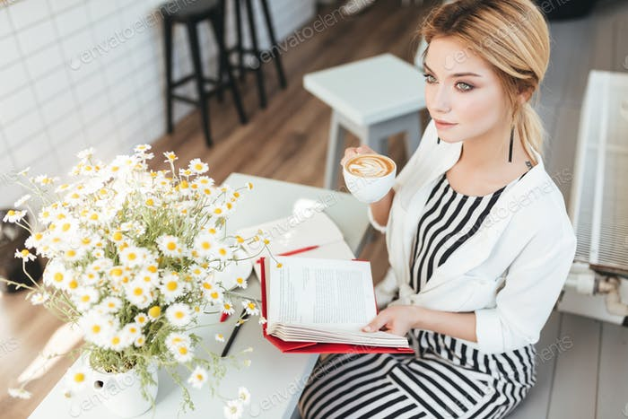 Young lady with blond hair drinking cappuccino in coffee shop with big bouquet of chamomile