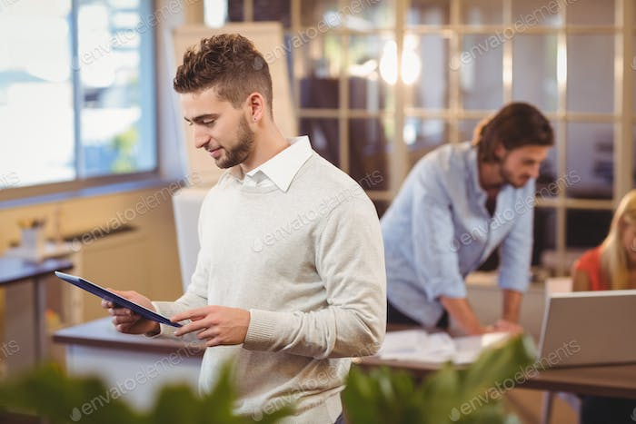 Businessman using digital PC with colleagues working in background in creative office