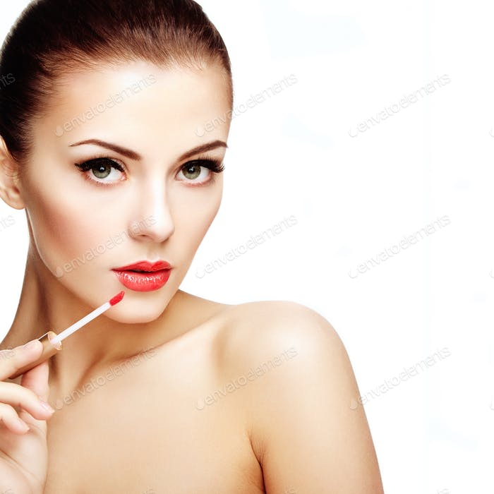 Beautiful young woman paints lips with lipstick