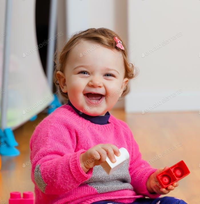 Kleinkind Baby Mädchen spielen mit Gummi-Bausteinen.
