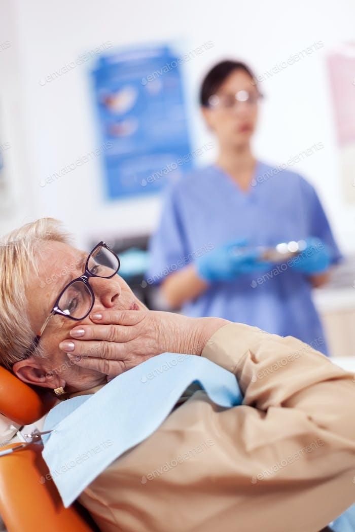 Patienten mittleren Alters berühren Mund mit schmerzhaften Ausdruck