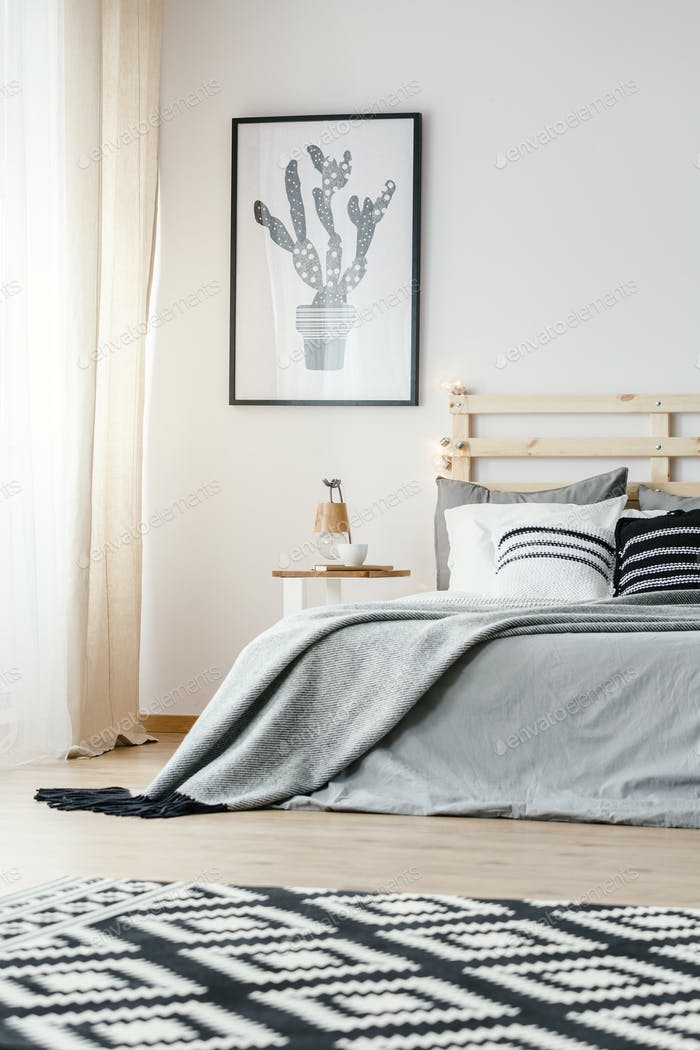 Patterned carpet and poster in grey simple bedroom interior with