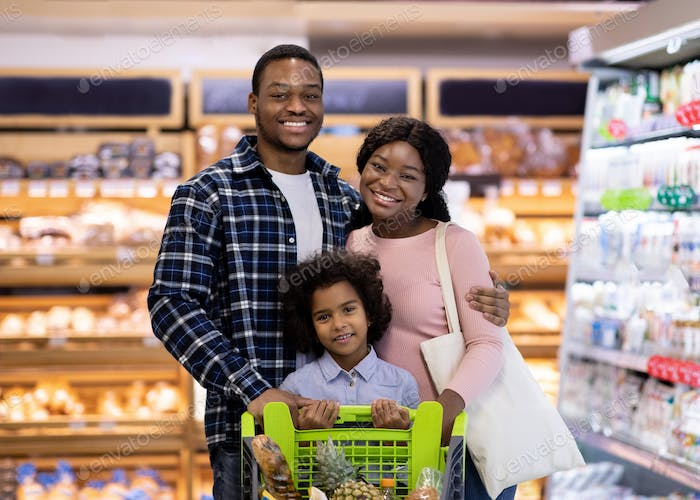 Portrait of smiling black parents with their daughter purchasing groceries at big supermarket