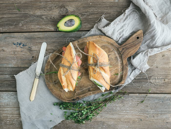 Salmon, avocado and thyme sandwiches in baguette tied up with decoration rope