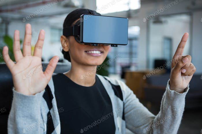 Smiling businesswoman using virtual reality headset