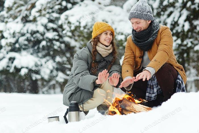 Schönes Paar sitzend durch Feuer im Winter