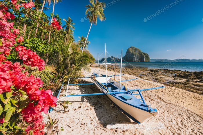 El Nido, Palawan, Philippines. Native banca boat and vibrant flowers at Las cabanas beach with