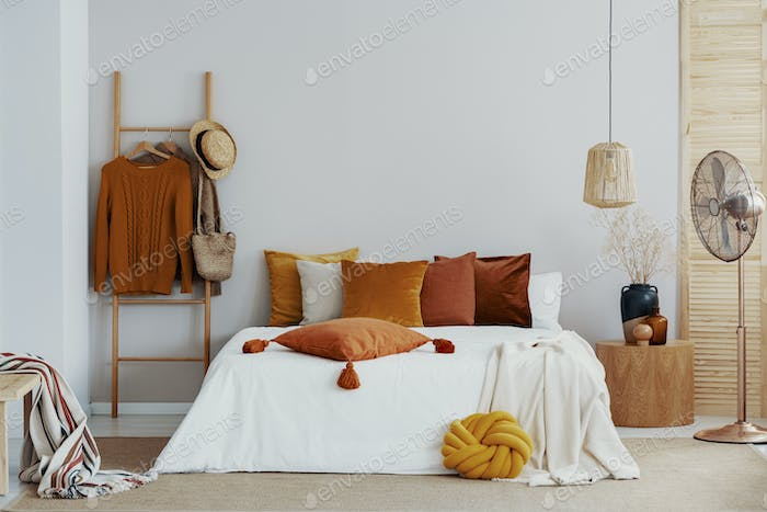 Autumn colors in bright natural bedroom with wooden accents, cop