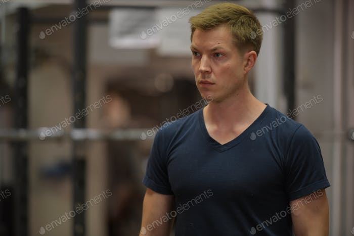 Young handsome Scandinavian man thinking at the gym