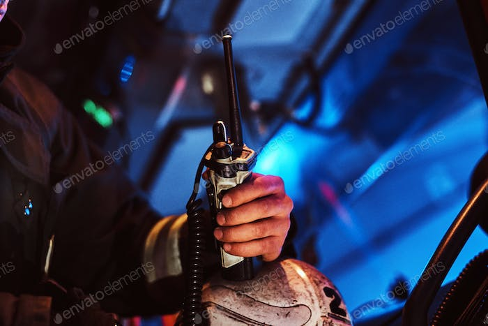 Fireman in a protective uniform sitting in the fire truck and holding walkie-talkie. Hand close up.
