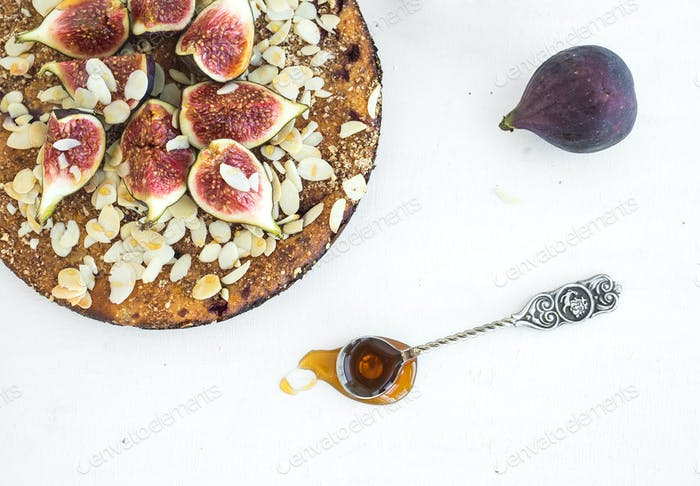Fig cake with fresh figs, honey and almond on white
