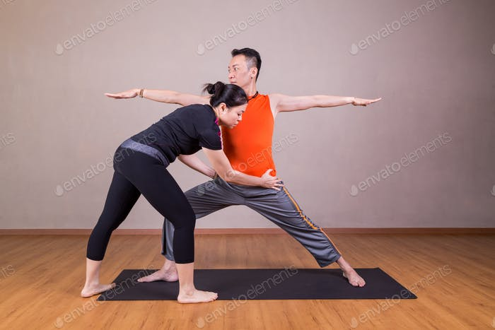 Yoga instructor correcting student performing Warrior 2 or Virab