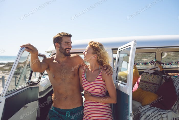 Thumbnail for Happy Caucasian couple talking with each other near camper van at beach in the sunshine