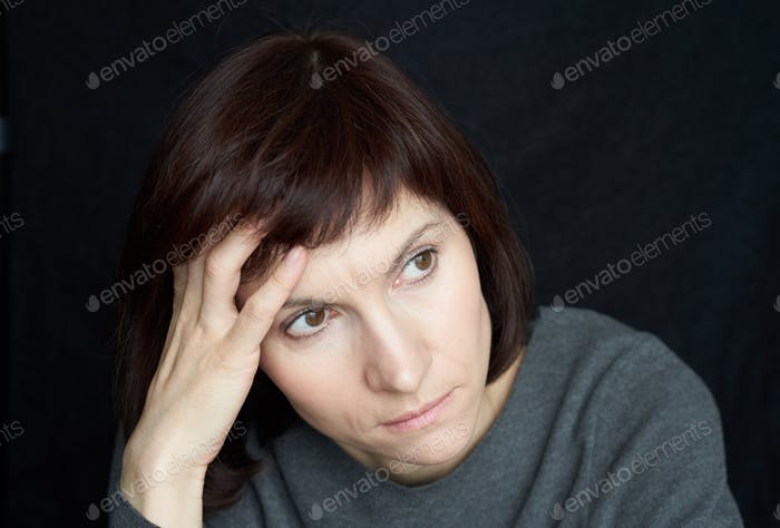 Mature, middle-aged woman looks anxiously away, touching forehead and hair with hand