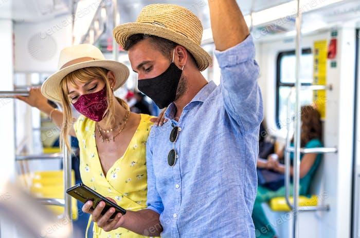 Bild eines glücklichen Paares, das während der Pandemieereignisse 2020 im U-Bahn-Pendler reist