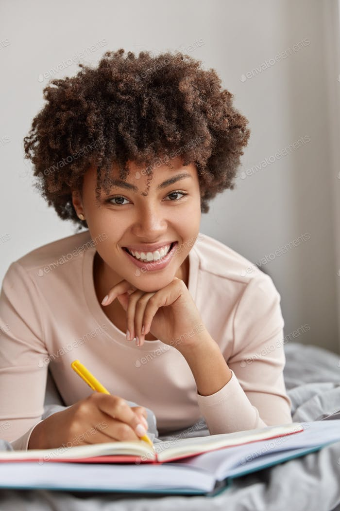 Shot of cheerful Afro American woman has toothy smile, lies at bed, writes down notes in notepad, be