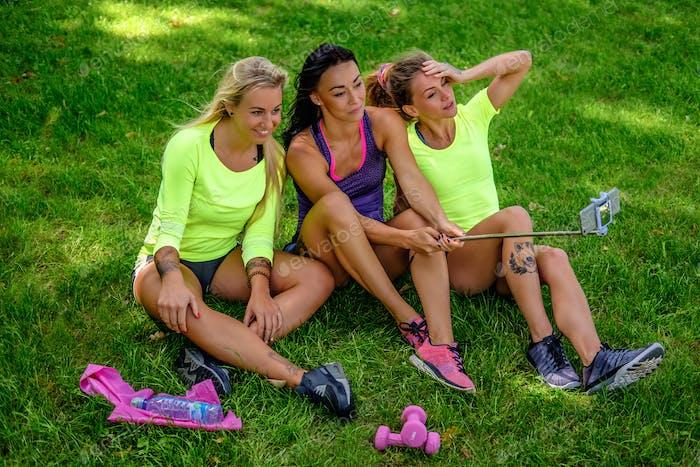 Drei sportliche Weibchen sitzen auf einem Rasen und machen Selfie.