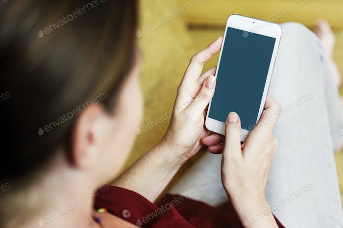 Woman using smartphone on sofa