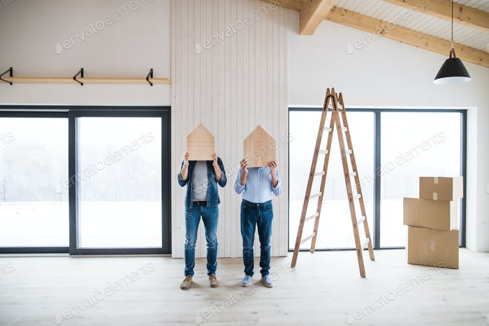 Men holding wooden houses on their heads when furnishing new house, a concept.