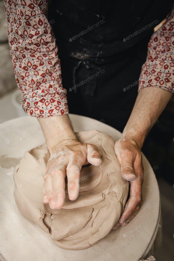 Potter master mashing the clay