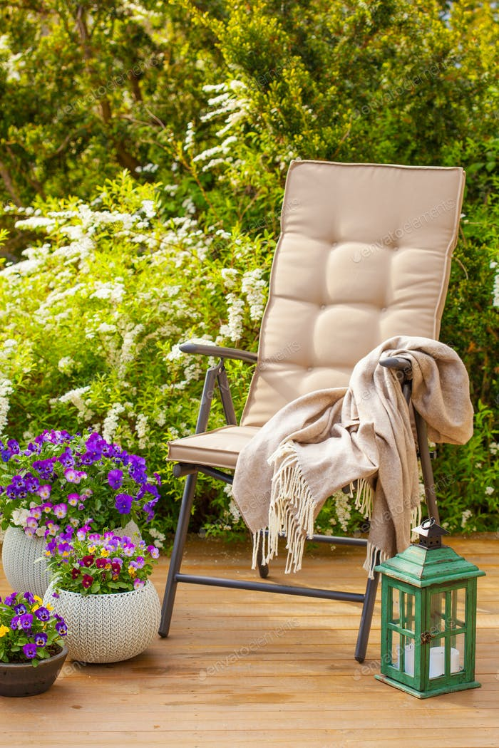 garden chair on terrace in sunlight, pansy flowers