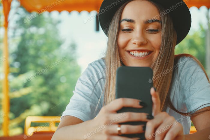 Young hipster girl in trendy hat holding smartphone in hands smi