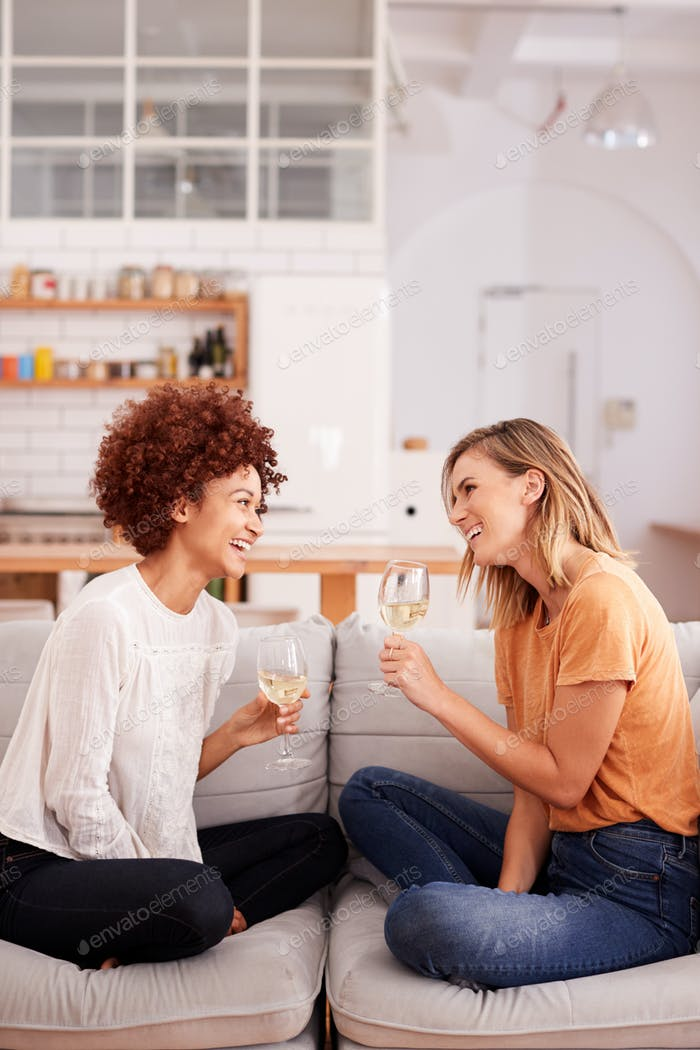 Two Female Friends Relaxing On Sofa At Home With Glass Of Wine Talking Together