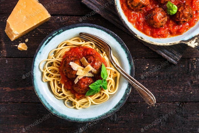 Pasta with meatballs and tomato sauce and cheese, top view, rustic style