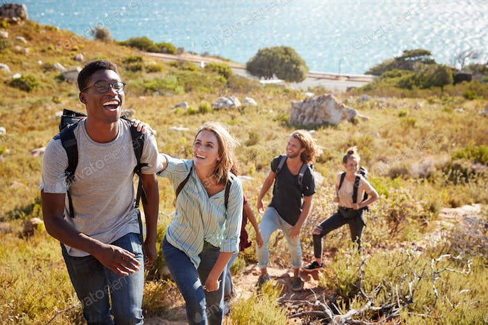 Millennial African American man leading friends hiking single file uphill on a path by the coast