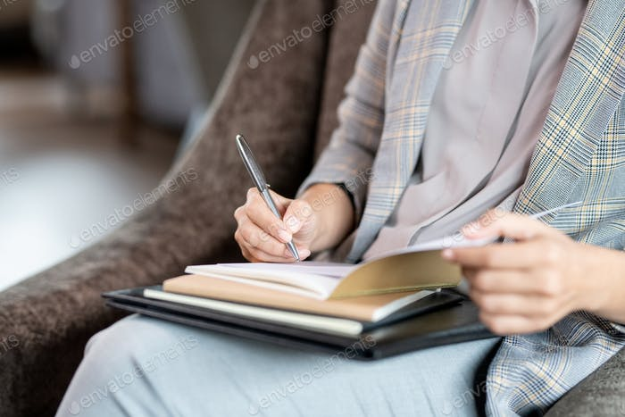 Hands of young elegant businesswoman with pen over page of copybook