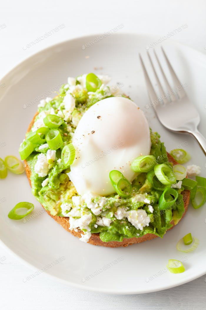 breakfast avocado sandwich with poached egg and feta cheese