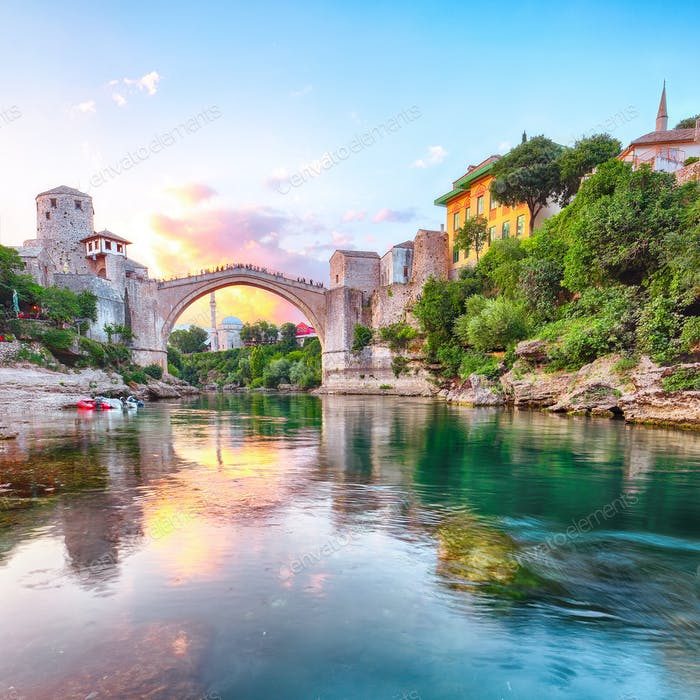 Fantastic Skyline of Mostar with the Mostar Bridge, houses and minarets, at sunset