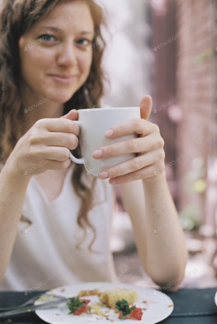 Smiling woman holding a white china teacup.