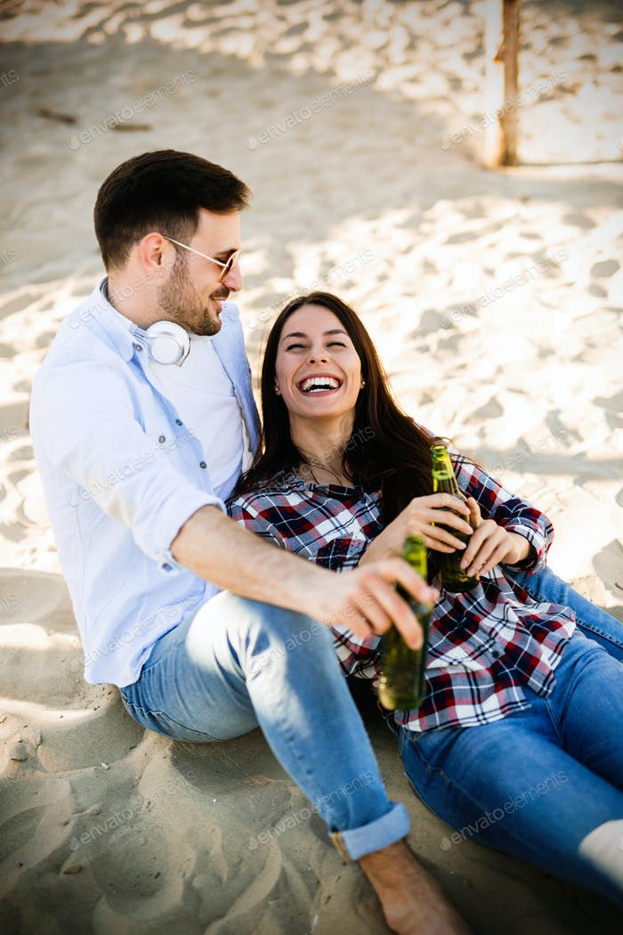 Happy couple smiling and drinking beer at beach