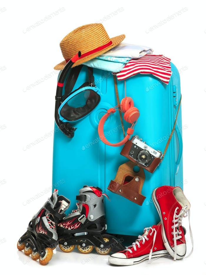 The blue suitcase, sneakers, clothing, hat, and retro camera on white background.