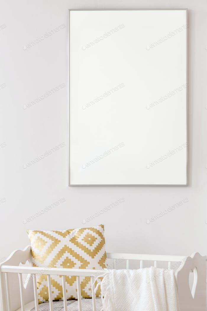 White poster mockup over baby cradle