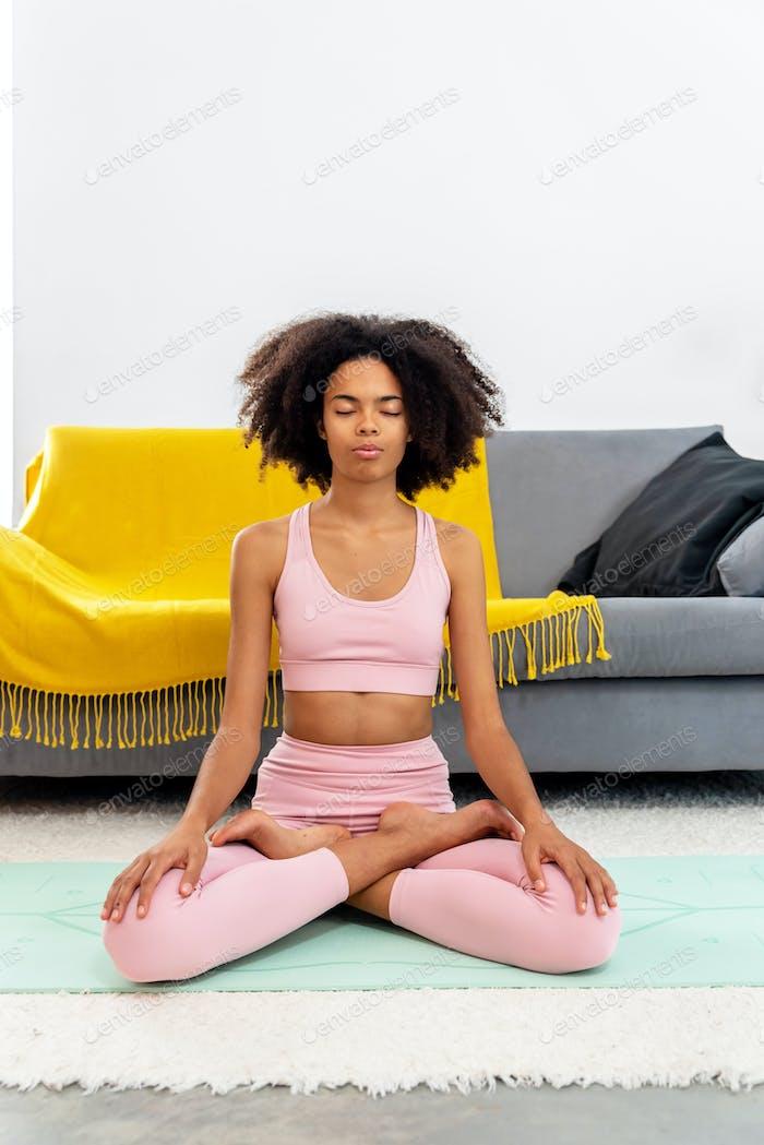 Afroamerikanische Frau praktiziert Yoga Lotus Pose zur Meditation in gemütlichem Zuhause