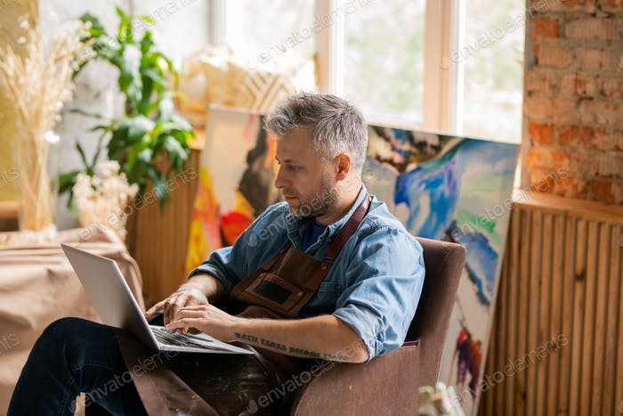 Serious artist with laptop sitting in armchair in studio and surfing in the net