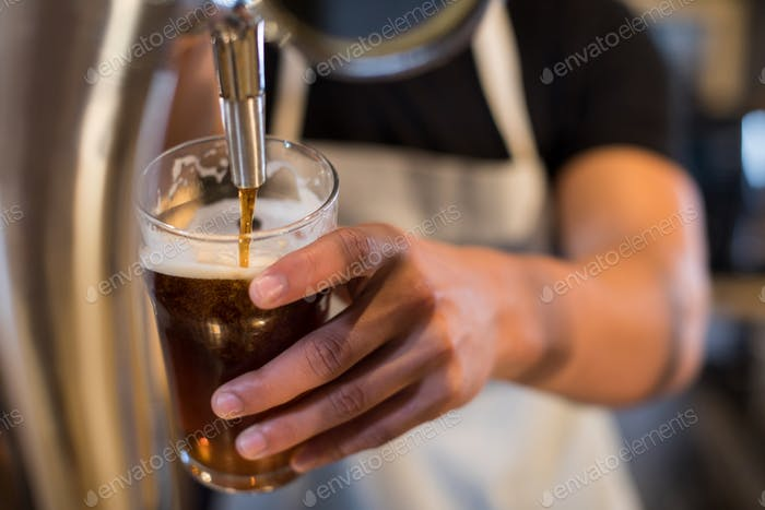 Midsection bartender pouring beer from tap