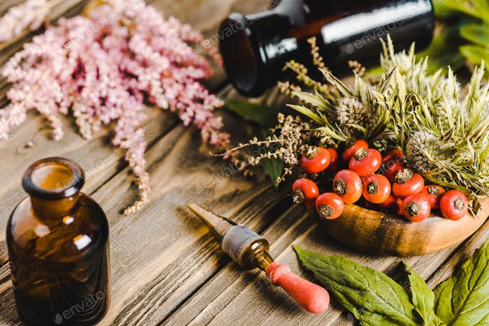 glass jars and flowers on wooden tabletop, alternative homeopathy medicine concept