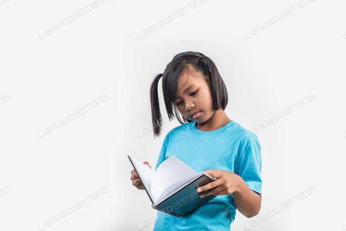little girl reading book in studio shot