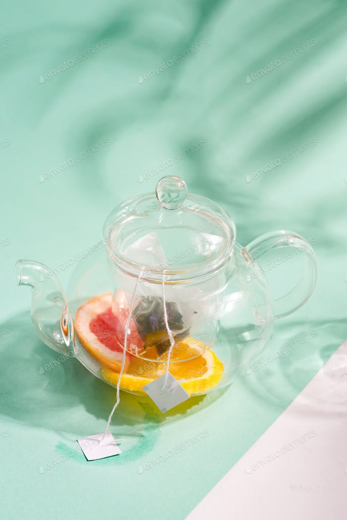 Glass teapot with ingredients for preparation cold summer homemade fruit tea on a duotone background