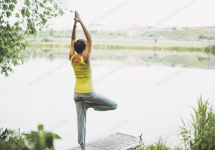 Junge lächelnde Frau Praxis Yoga im Freien