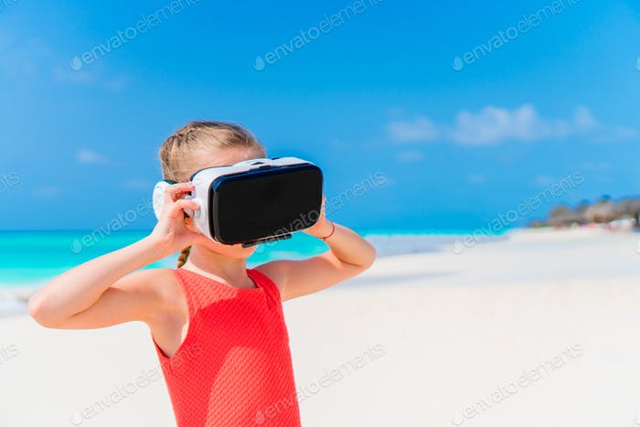 Cute little child girl using VR virtual reality goggles. Adorable girl look into the virtual glasses