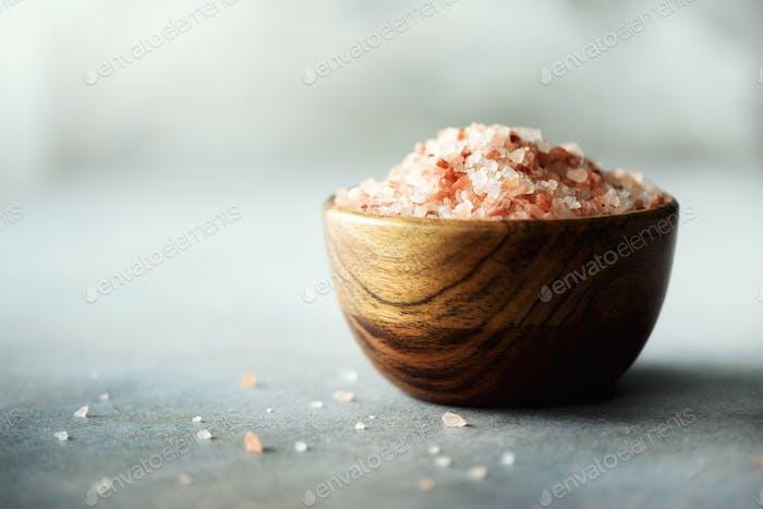 Rosa Himalaya-Salzkristalle und Pulver in Holzschalen auf grauem Betonuntergrund. Gesunde Ernährung