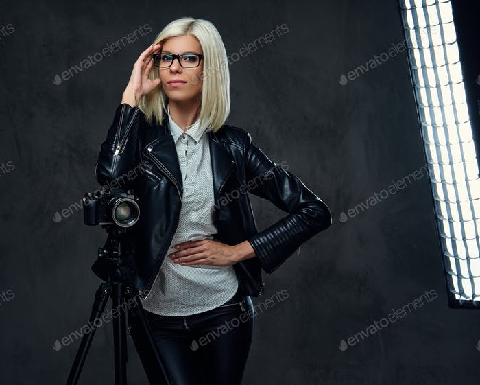 Blond photographer female on a grey background.
