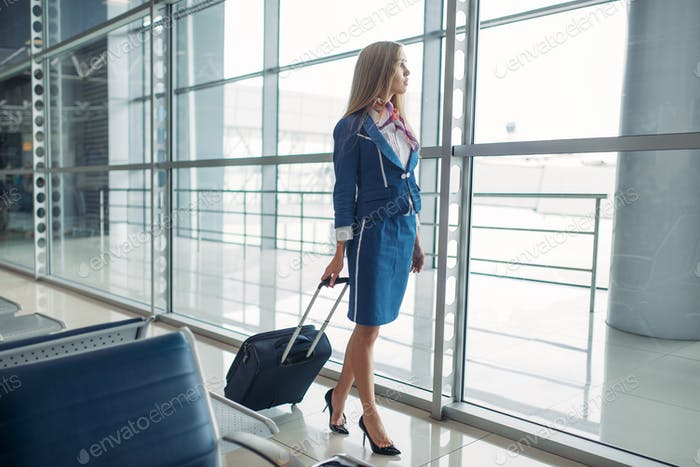 Stewardess with suitcase in airport waiting room