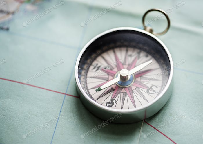 Closeup of metallic compass on the map journey planning