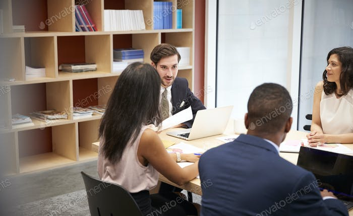 Four business people at a boardroom meeting