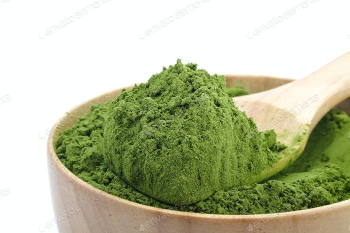 Grüner Teepulver in Holzlöffel auf weißem Hintergrund.
